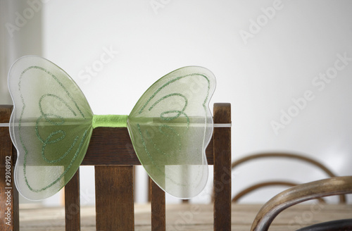 Empty chair with butterfly decor on back