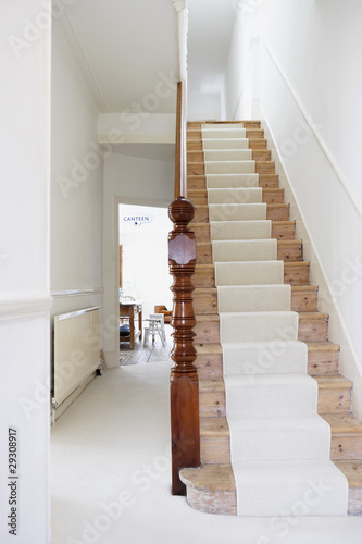 Staircase with runner and empty hallway