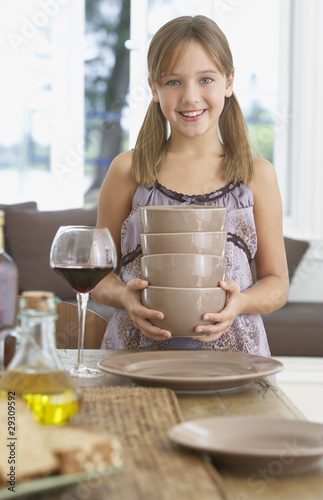 Young girl in dining room setting table