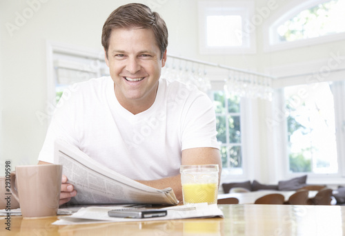Man in kitchen with newspaper