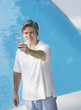 Man outdoors by swimming pool with his mobile phone