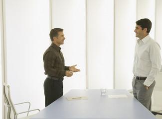 Two businessmen in a boardroom talking