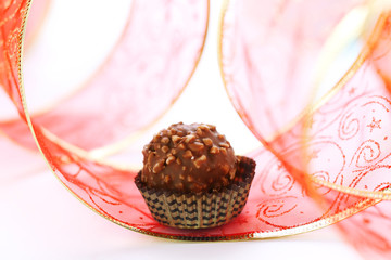 Chocolate truffle with red ribbon closeup