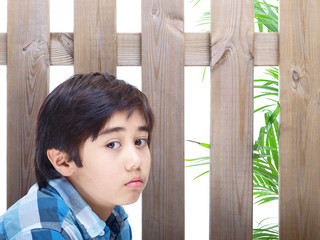 child sitting in front of a wooden fence