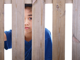 child looking through a fence