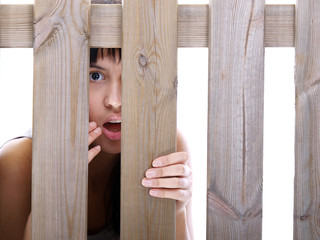 girl peeking through the fence