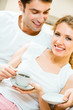 Young happy couple drinking coffee together at home