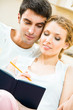 Young attractive couple with notebook or organizer at home