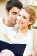 Young happy couple with notebook or organizer at home