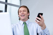 Happy young businessman holding a mobile phone
