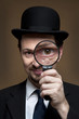 I find you!!! -man with bowler looking through a magnifier.