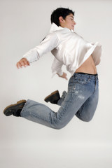 young teenage boy jumping in jeans and white shirt