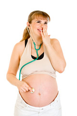 Surprised pregnant woman holding stethascope on her tummy