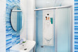 Modern blue bathroom interior with round mirror and shower cubic