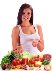 Young woman standing at the table with fresh raw vegetables
