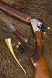 shotgun, cartridges, knife and hunt on top of a boar skin poster
