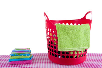 red laundry basket with folded was on an ironing board isolated