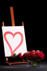 Roses bouquet and canvas with heart outline isolated on black