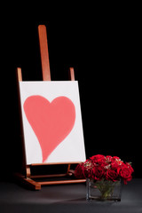 Roses bouquet and canvas with heart shape isolated on black