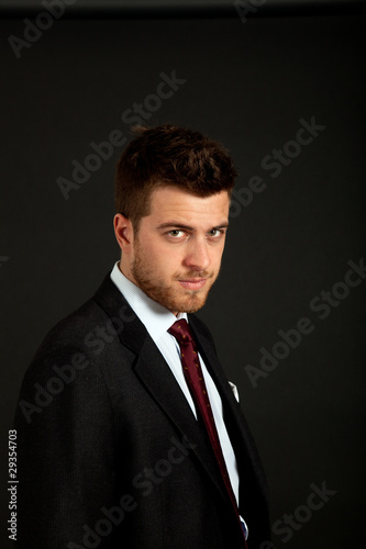 Young businessman portrait on a dark background