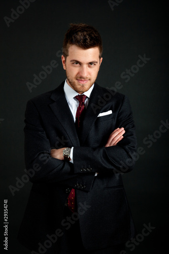 Confident businessman portrait on dark background