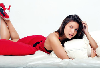 Woman in red dress in bed