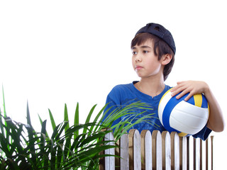 boy holding a ball leaning on the fence
