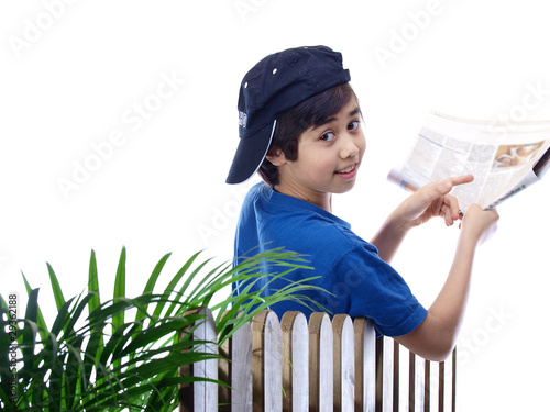 smiling boy leaning over the fence with a newspaper