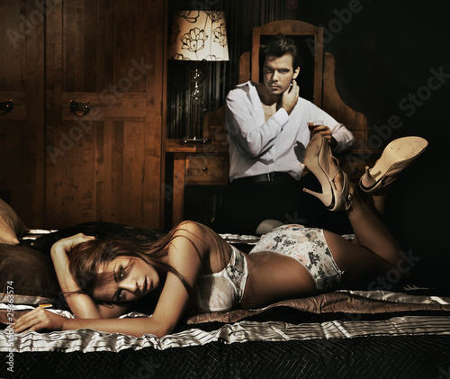 Two adult people in bedroom posing