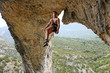 Rock climber hanging on the rope after reaching the top