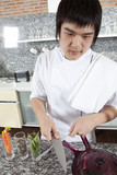 Asian young chef sharpening a knife brutally. poster