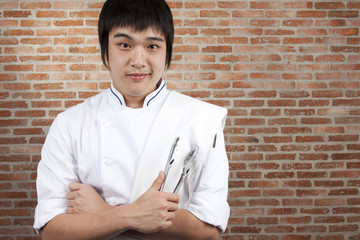 Asian young chef crossing arms holding kitchen utensil.