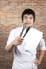 Asian young chef smile and holding kitchen utensil.