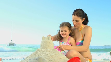 Attractive mother helping her daughter to build a sand castle