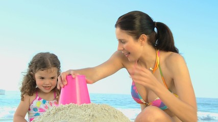 Cute daughter building a sand castle with her mother
