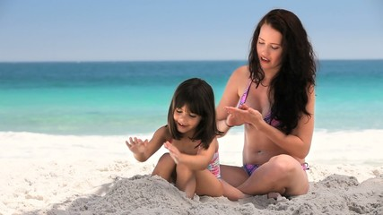 Attractive woman putting sunscreen on her daughter