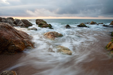 Seascape at sunset with motion blurred waves crashing on rocks