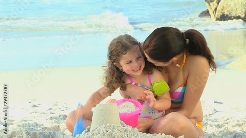 Mother helping her daughter to build a sand castle