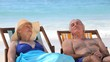 Aged couple relaxing on beach chairs
