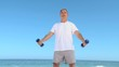 Aged man working his muscles with dumbbells