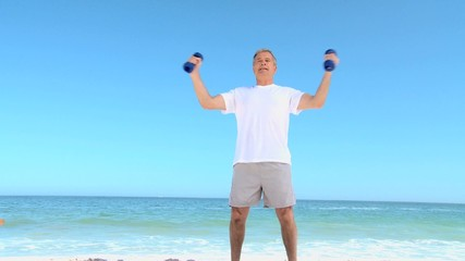 Mature man working his muscles with dumbbells