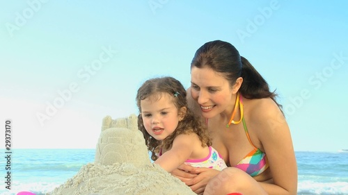 Cute girl building a sand castle with her mother