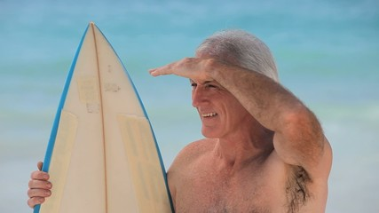 Closeup of a senior man looking at the ocean with a surfboard