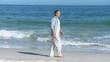 Elderly man walking along the beach