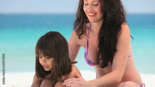 Mother putting sunscreen on her daughter