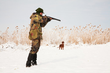 Hunter aiming at the prey, dog waiting