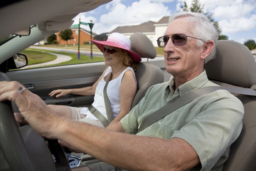 Senior Couple Driving Convertible Car Wearing Sunglasses