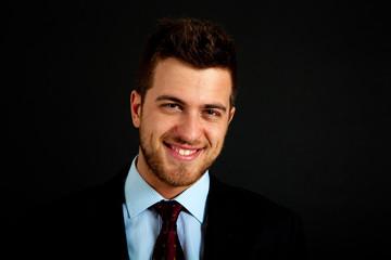 Smiling successful businessman on dark background