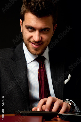 Vicious businessman using calculator on dark background