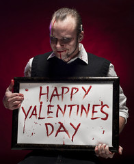 Man holding a happy valentine's sign written with blood.
